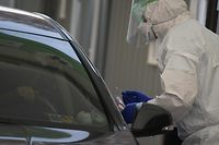 A health worker (R) wearing a protective suit prepares a swab for a motorist (L) at a drive-through testing centre for the COVID-19 coronavirus in Seoul on March 7, 2020. - South Korea has the biggest number of COVID-19 coronavirus cases outside China, with over 6,000 infections and 42 deaths, prompting the country to extend school breaks by three weeks. (Photo by Ed JONES / AFP)
