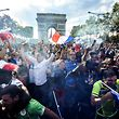 This picture taken from the terrace of the Publicis drugstore  on July 15, 2018 shows people celebrating on the Champs-Elysees avenue in front of the Arch of Triumph (Arc de Triomphe) in Paris, after France won the Russia 2018 World Cup final football match between France and Croatia. / AFP PHOTO / GERARD JULIEN