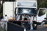 (FILES) This file photo taken on July 15, 2016 shows forensics officers and policemen looking for evidences near a truck on the Promenade des Anglais seafront in the French Riviera town of Nice after it drove into a crowd watching a fireworks display. Nice will commemorate on July 14, 2017 the first anniversary of the attack committed against the crowd that celebrated Batille day. For the past year, the question of security measures deployed on the Promenade des Anglais before the attack that caused the death of 86 people is at the heart of a polemic and torments survivors and relatives of the victims, who are relying on the investigation to obtain answers. / AFP PHOTO / ANNE-CHRISTINE POUJOULAT