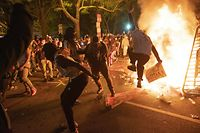 TOPSHOT - Protesters jump on a street sign near a burning barricade during a demonstration against the death of George Floyd near the White House on May 31, 2020 in Washington, DC. - Thousands of National Guard troops patrolled major US cities after five consecutive nights of protests over racism and police brutality that boiled over into arson and looting, sending shock waves through the country. The death Monday of an unarmed black man, George Floyd, at the hands of police in Minneapolis ignited this latest wave of outrage in the US over law enforcement's repeated use of lethal force against African Americans -- this one like others before captured on cellphone video. (Photo by ROBERTO SCHMIDT / AFP)