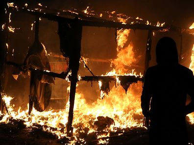 """A migrant look at a shack set on fire during the demolition of the Calais """"Jungle"""" camp, in Calais, northern France, on October 25, 2016 as hundreds of migrants boarded buses on the second day of a massive operation to clear the squalid settlement. More than 1,900 left the slum on October 24, ahead of work to tear down the makeshift shelters and eateries in the camp that has become a symbol of Europe's refugee crisis. / AFP PHOTO / Fran�ois NASCIMBENI"""