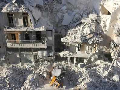 A tractor clears the rubble following Syrian govermnet forces airstrikes in the rebel held neighborhood of Tariq a-Bab in Aleppo on September 24, 2016.