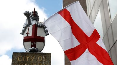 A St George's Cross flag flies from a City of London boundary marker.