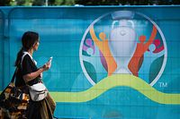 A pedestrian walks past the logo of the UEFA EURO 2020 European Football Championship in Copenhagen, one of the tournament's host cities, on June 10, 2021. (Photo by JONATHAN NACKSTRAND / AFP)