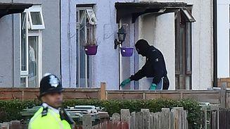 An investigator enters a house during a police raid in Sunbury, Surrey near London.