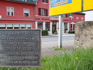 """Links stark vergrößert die Plakette, die an der Eingangstür des """"Hotel de la frontière"""" in Frisingen hängt. Rechts im Bild der verwitterte Grenzstein, der genau vor dem Hotel die Abgrenzung zwischen Frankreich und Luxemburg zieht."""