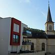 Manche der neuen Wohnungen liegen in der Tat sehr nahe am Kirchturm. Doch dürfte es keinen Zweifel geben, welches Gebäude länger in der Ortschaft steht.