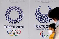 Pedestrians pass the logo of the Tokyo 2020 Olympic Games and Paralympic Games at a subway station in Tokyo on March 24, 2020. - The International Olympic Committee came under pressure to speed up its decision about postponing the Tokyo Games on March 24 as athletes criticised the four-week deadline and the United States joined calls to delay the competition. (Photo by Kazuhiro NOGI / AFP)