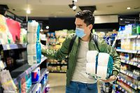 Panic buying toilet paper during Coronavirus. Young Man shopping in a supermarket, breathing through a medical mask because of the danger of getting the flu virus, influenza infection. Corona virus pandemic concept. Covid-19 virus!