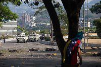 30.04.2019, Venezuela, Caracas: Ein Demonstrant sucht Schutz hinter einem Baum, während Demonstranten mit Sicherheitskräften des venezolanischen Staates zusammenstoßen. Der venezolanische Oppositionsführer Guaido und der inhaftierte Oppositionsführer Lopez riefen Soldaten und die Bevölkerung dazu auf, gegen die Regierung auf die Straßen zu gehen. Foto: Ruben Sevilla Brand/dpa +++ dpa-Bildfunk +++