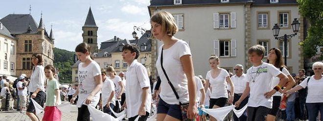 Die Teilnehmer der Prozession bewegen sich springend von einem Bein auf das andere vorwärts und seitwärts.