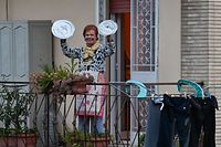"""TOPSHOT - A residents uses pot lids to play cymbals as she takes part in a music flash mob called """"Look out from the window, Rome mine !"""" (Affacciati alla Finestra, Roma Mia !) aimed at liven up the city's silence during the new coronavirus lockdown, from her balcony in Rome on March 13, 2020. (Photo by Andreas SOLARO / AFP)"""