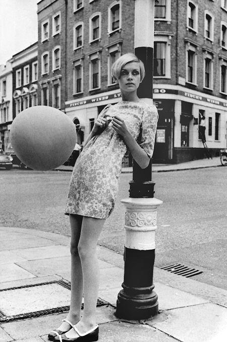 Gegen einen Laternenpfahl gelehnt, posiert Twiggy in den 1970er-Jahren für einen Fotografen.