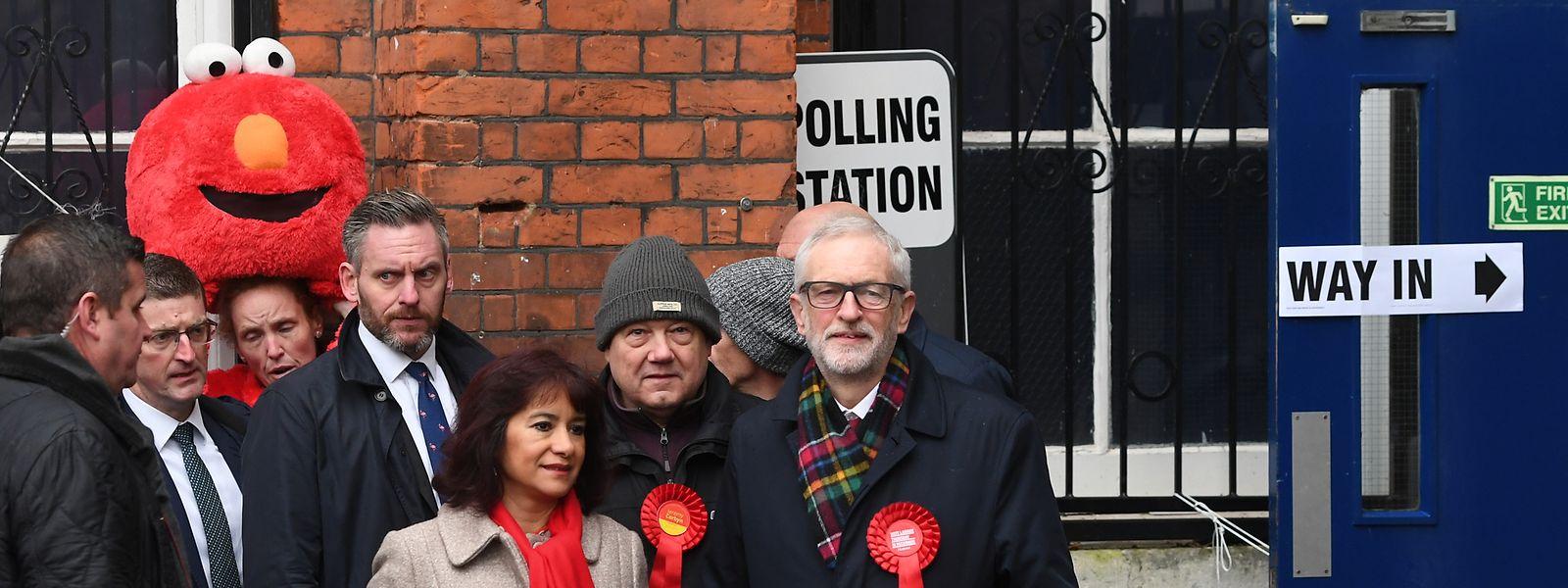 """Jeremy Corbyn im Wahllokal. Im Hintergrund links steht Bobby Smith, Gründer der Partei """"Give Me Back Elmo""""."""