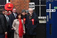 12.12.2019, Großbritannien, London: Jeremy Corbyn (r), Vorsitzender der Labour Party, und seine Frau Laura Alvarez treffen im Wahllokal in der Pakeman Primary School in Islington ein, im Hintergrund links steht Bobby Smith, politischer Aktivist für die Rechte von Vätern sowie Gründer der Partei «Give Me Back Elmo», mit seiner Maske. Die Briten wählen an diesem Donnerstag neue Abgeordnete und bestimmen damit indirekt auch, wie es mit dem geplanten EU-Austritt weitergehen soll. Die Wahllokale sind von 08.00 Uhr (MEZ) bis 23.00 (MEZ) geöffnet. Foto: Joe Giddens/PA Wire/dpa +++ dpa-Bildfunk +++