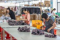 This picture taken on May 14, 2019 shows workers making clothes for export at a factory in Quanzhou in China's eastern Fujian province. (Photo by STR / AFP) / China OUT