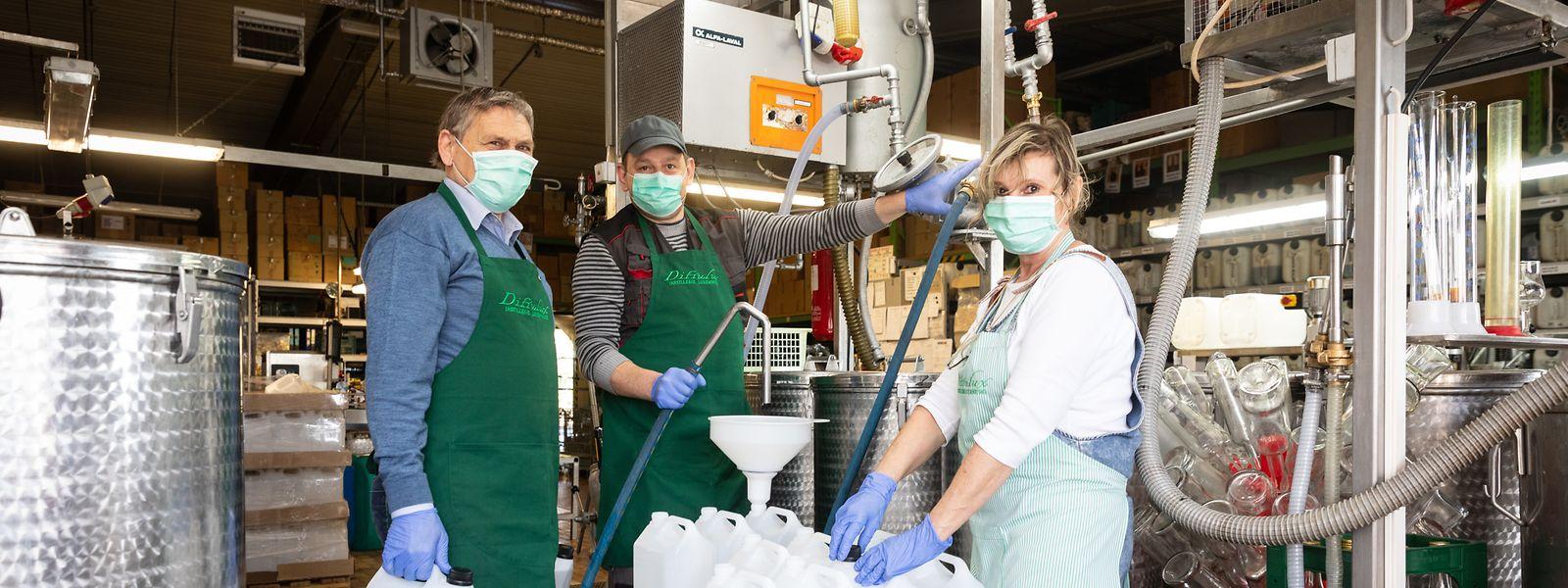 Gesundheit geht vor: Mit Maske, Handschuhen und Arbeitskittel stellen Firmenchef Gérard Leuchter (l.) und seine Mitarbeiter Anja Greskowia und Darek Govski in Breidweiler Desinfektionsmittel her.
