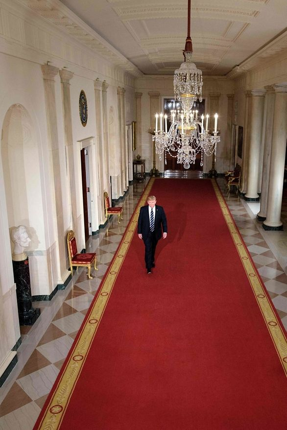 US President Donald Trump walks through the Cross Hall to the East Room at the White House