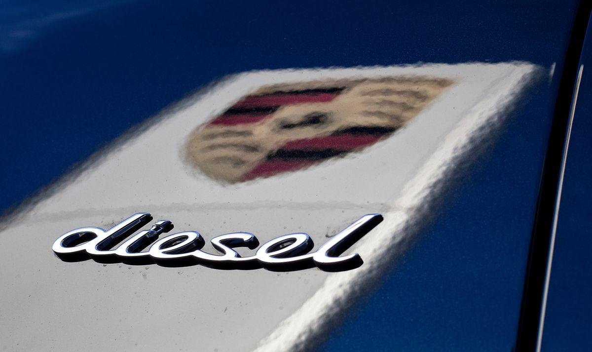 Als erster deutscher Autokonzern steigt Porsche aus dem Diesel aus: Das Logo des Fahrzeugherstellers der VW-Tochter in der dunklen Lackierung eines Porsche Cayenne, während dabei der Schriftzug «Diesel» auf dem Wagen zu sehen ist.
