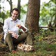 HANDOUT - 09.10.2015, Frankreich, Vencimont: Maxime Collard sitzt vor einem Korb mit Pilzen in einem Wald. Unter dem Begriff «Generation W» sind 24 Spitzenköche aus der belgischen Wallonie vereint - unter ihnen der Sterne-Chef Maxime Collard. (zu dpa «Generation W»: Belgische Spitzenköche setzen auf Regionalität vom 06.10.2018) Foto: -/dpa - ACHTUNG: Nur zur redaktionellen Verwendung im Zusammenhang mit der Berichterstattung und nur mit vollständiger Nennung des vorstehenden Credits +++ dpa-Bildfunk +++