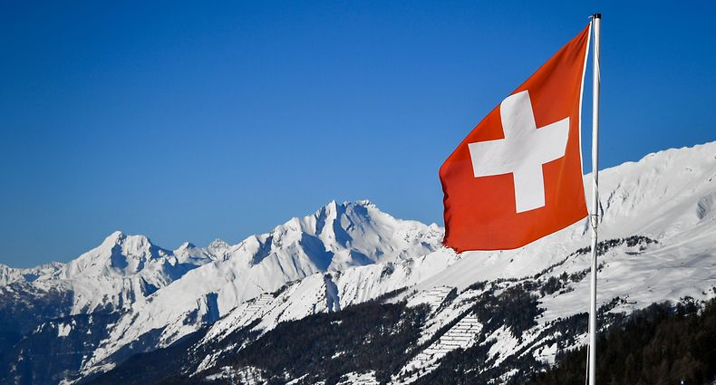 "A Swiss flag flutters on March 4, 2018 in Crans-Montana above the Rhone valley in the Swiss canton of Valais, location of Sion, a city of some 34,000 souls bidding to host the 2026 Winter Olympic Games. The official race to succeed 2018 hosts Pyeongchang, and Beijing in 2022 begins in March when would be candidates file ""letters of intention"" to the International Olympic Committee. / AFP PHOTO / Fabrice COFFRINI"