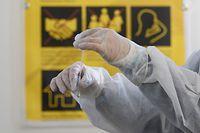 12.05.2021, Sachsen, Dresden: Eine Mitarbeiterin im Corona-Testzentrum der SG Dynamo Dresden wertet einen Antigen-Schnelltest auf das Coronavirus aus. Die SG Dynamo Dresden hat im Rahmen eines Pilotprojektes das Corona-Testzentrum eröffnet. Dort können sich ab sofort nicht nur Dynamo-Fans, sondern Nachwuchssportler und auch alle anderen Menschen auf das Corona-Virus testen lassen. Foto: Robert Michael/dpa-Zentralbild/dpa +++ dpa-Bildfunk +++