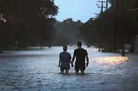 MANDEVILLE, LOUISIANA - JULY 13: A couple strolls down Lakeshore Drive along the shore of Lake Pontchartrain after it was flooded in the wake of Hurricane Barry on July 13, 2019 in Mandeville, Louisiana. The storm, which made landfall this morning as a category one hurricane near Morgan City, caused far less damage and flooding than had been predicted. Flash flood watches were issued throughout much of Louisiana and as far east as the Florida panhandle as the storm was expected to dump more than a foot of rain in many areas and up to 25 inches in some isolated locations. Many areas are now expected to get less than half of the original projections.   Scott Olson/Getty Images/AFP == FOR NEWSPAPERS, INTERNET, TELCOS & TELEVISION USE ONLY ==