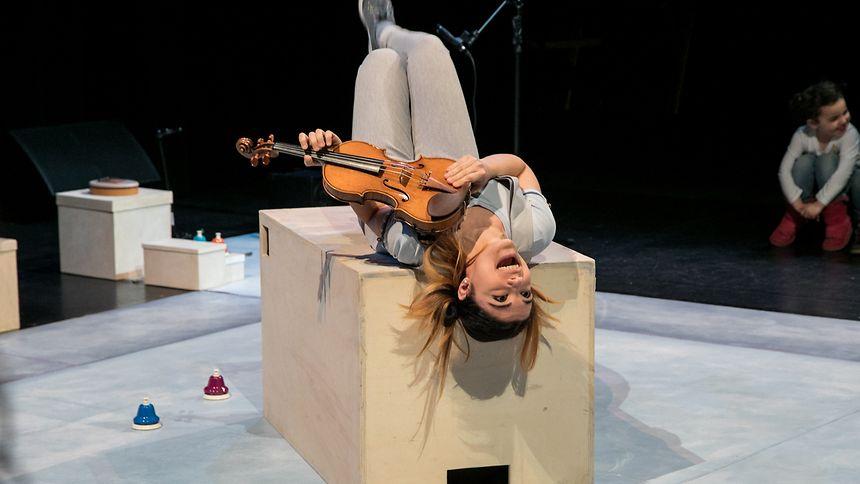 Musikalisch erkundet Eleonora die Bühne: eine Welt aus Pappkisten, Klingeln und der Violine.