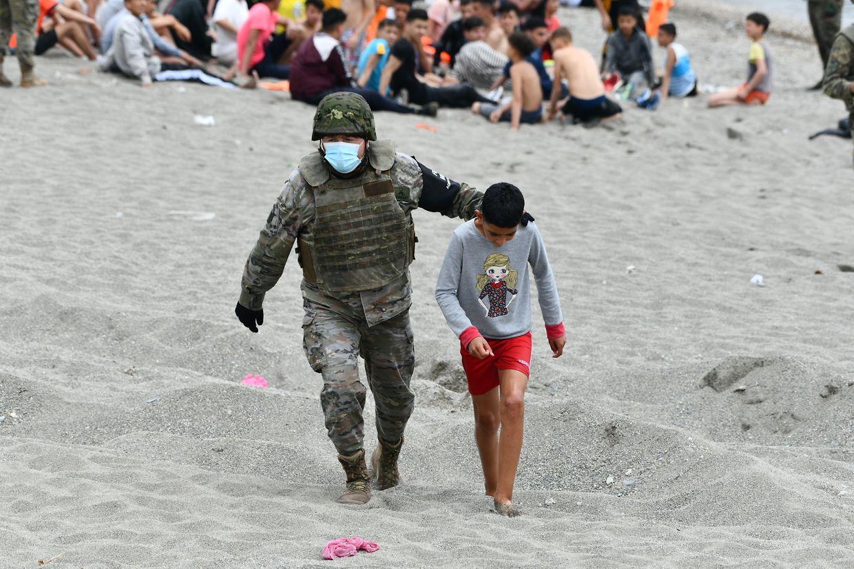 Ein spanischer Soldat begleitet ein Kind nach seiner Ankunft in Ceuta. Innerhalb von 36 Stunden gelangten rund 8000 Menschen in das kleine Gebiet im Nordwesten von Marokko. Die Zahl der wieder nach Marokko abgeschobenen Menschen erhöhte sich unterdessen auf circa 5600.