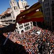 """Protesters hold Spanish flags from a balcony during a demonstration called by """"Societat Civil Catalana"""" (Catalan Civil Society) to support the unity of Spain on October 8, 2017 in Barcelona. Spain braced for more protests despite tentative signs that the sides may be seeking to defuse the crisis after Madrid offered a first apology to Catalans injured by police during their outlawed independence vote. / AFP PHOTO / PAU BARRENA"""