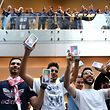 First customers display their iPhone X sets at an Apple showroom in Sydney on November 3, 2017.  Apple iPhone X went for sale in Australia with long queues outside the Apple stores.  / AFP PHOTO / SAEED KHAN