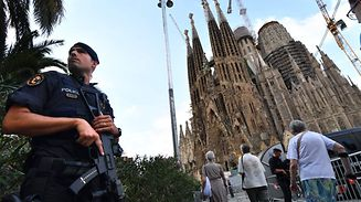 "TOPSHOT - A police officer stands by the Sagrada Familia basilica in Barcelona on August 20, 2017, before a mass to commemorate victims of two devastating terror attacks in Barcelona and Cambrils. A grief-stricken Barcelona prepared today to commemorate victims of two devastating terror attacks at a mass in the city's Sagrada Familia church. As investigators scrambled to piece together the attacks which killed 14 people in all, Interior Minister Juan Ignacio Zoido said on August 19 the cell behind the carnage that also injured 120 and plunged the country into shock had been ""dismantled,"" though local authorities took a more cautious tone.   / AFP PHOTO / PASCAL GUYOT"