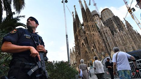 A police officer stands by the Sagrada Familia basilica in Barcelona before a mass to commemorate victims of two terror attacks in Barcelona and Cambrils.