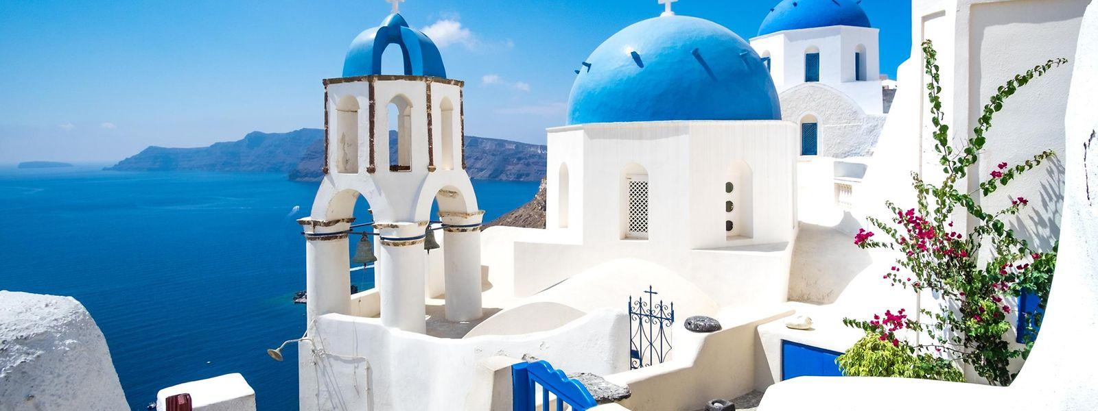 Immer ein Reise-Highlight: die weiß getünchten Häuser der Insel Santorini mit ihren blauen Kuppeldächern und der Aussicht auf das Meer in ebenso strahlendem Azurblau.
