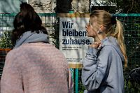 "Two woman walk by a restaurant with a sign up which reads ""We Stay at Home"" in Berlin's Kreuzberg district on March 27, 2020 during the new coronavirus COVID-19 pandemic. (Photo by David GANNON / AFP)"