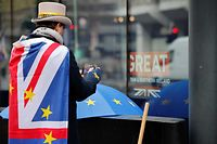 Anti-Brexiteer activist Steve Bray looks at his mobile phone as he protests outside a conference centre in central London on December 4, 2020, as talks continue on a trade deal between the EU and the UK. - With just a month until Britain's post-Brexit future begins and trade talks with the European Union still deadlocked, the UK government on Tuesday urged firms to prepare as it scrambles to finish essential infrastructure. (Photo by Tolga Akmen / AFP)