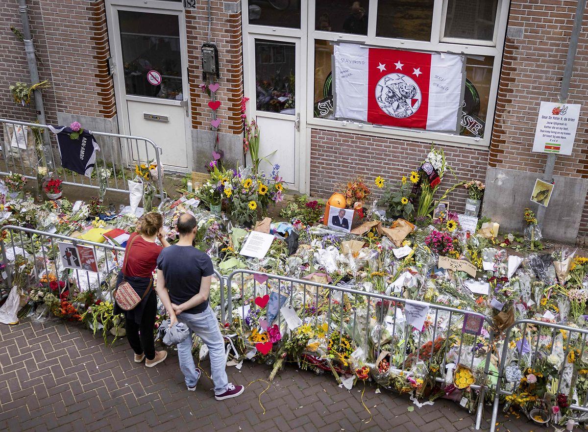 Menschen legen für Peter de Vries Blumen ab.