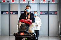 Passengers coming from China, leaves the Terminal wearing paper masks after landing in Charles De Gaule Airport on January 26, 2020. (Photo by Alain JOCARD / AFP)