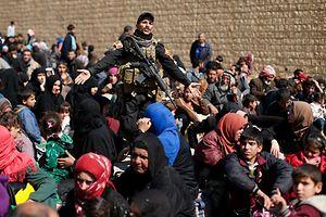 Un soldat irakien parmi des habitants de Mossoul. Sous les feux croisés de l'armée et des djihadistes, des milliers de personnes voudraient quitter la ville.