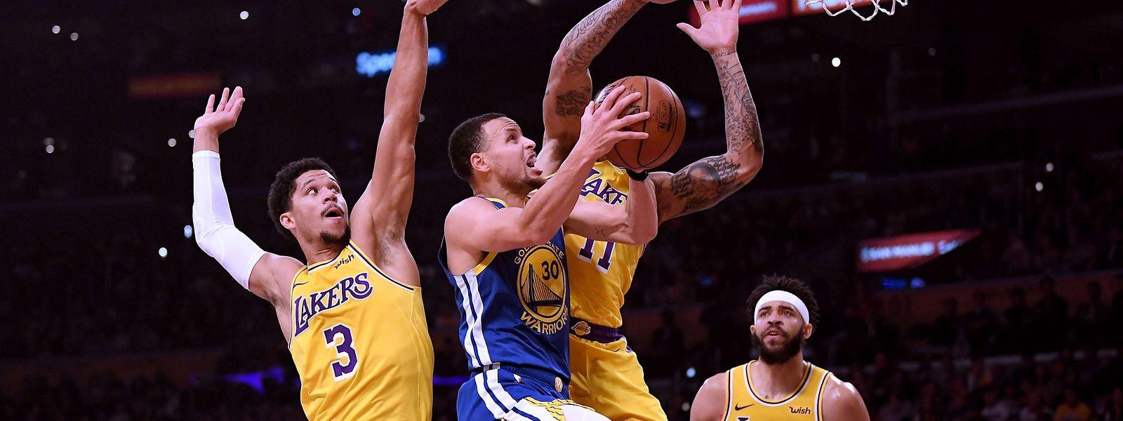 Stephen Curry (Golden State, n°30) est coincé sous l'anneau entre Josh Hart (n°3) et Michael Beasley (n°11), des Lakers
