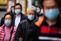 Pedestrians wear face masks in Hong Kong on February 3, 2020, as a preventative measure following a virus outbreak which began in the Chinese city of Wuhan. - Hundreds of Hong Kong medical workers walked off their jobs on February 3, demanding the city close its border with China to reduce the coronavirus spreading -- with frontline staff threatening to follow suit in the coming days. (Photo by Anthony WALLACE / AFP)