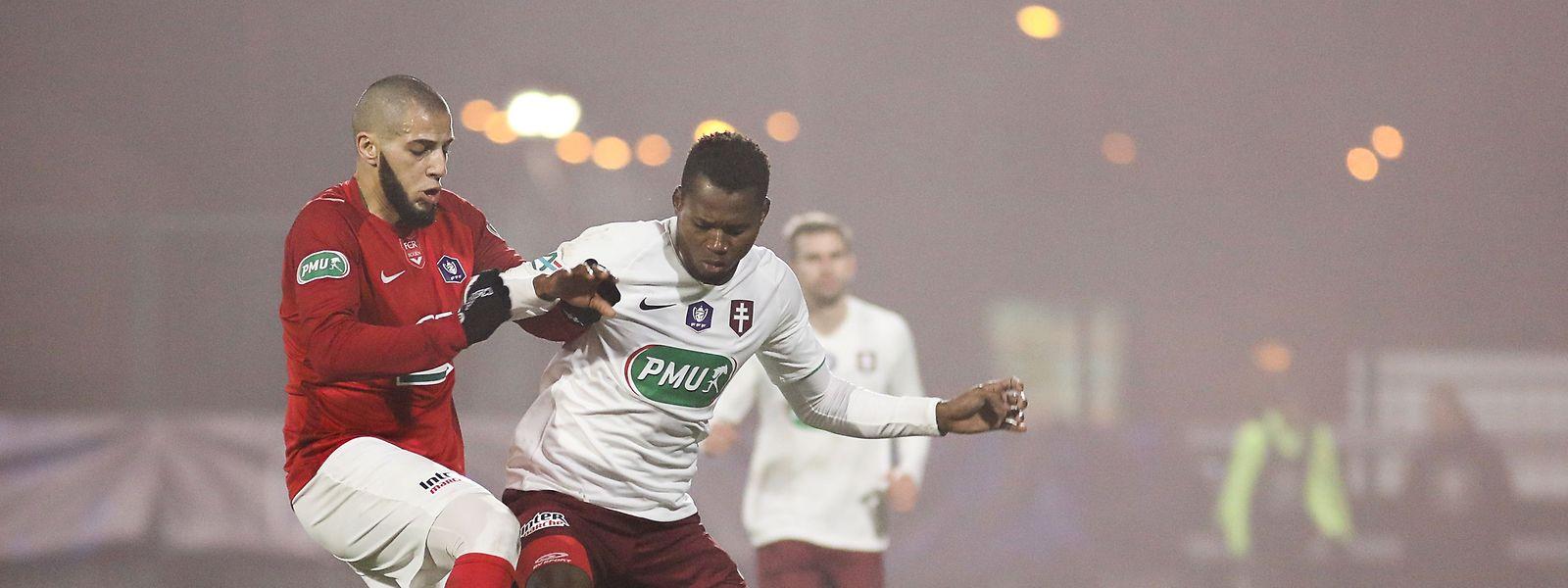 Opa Nguette verliert mit Metz gegen Rouen um Mustapha Benzia (l.).