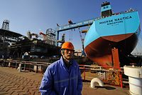 (FILES) This file photograph taken on February 15, 2008, shows a worker stands in front of an under-construction 300,000-tonne oil tanker for Danish shipping company Maersk and an under-construction offshore drilling platform at a shipyard in northeast China's city of Dalian.  French oil giant Total said on August 21, 2017, that it would buy Maersk Oil, a unit of the Danish shipping giant A.P. Moller-Maersk, for USD 7.45 billion. The company said the deal would make Total the second-largest operator in the North Sea, with substantial operations in Britain, Norway and Denmark.  / AFP PHOTO / TEH ENG KOON