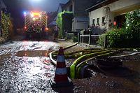 11.07.2019, Rheinland-Pfalz, Trier: Feuerwehrleute pumpen einen Keller im Stadtteil Olewig leer. Ein heftiges Unwetter mit starkregen und Hagel war über die Region hinweggefegt und flutete zahlreiche Strassen und Keller. Foto: Harald Tittel/dpa +++ dpa-Bildfunk +++