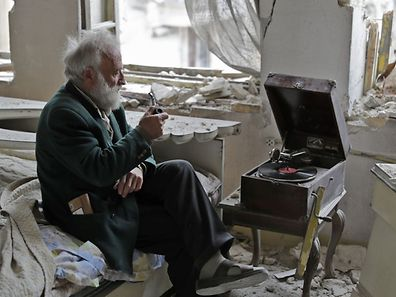 Mohammad Mohiedine Anis, 70, smokes his pipe as he sits in his destroyed bedroom listening to music on his vinyl player in Aleppo's formerly rebel-held al-Shaar neighbourhood on March 9, 2017. / AFP PHOTO / JOSEPH EID