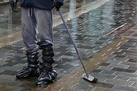 "TOPSHOT - A man wraps his feet in bin-liners as he cleans mud from the street in Pontypridd in south Wales on February 16, 2020, as Storm Dennis causes flooding across large swathes of Britain. - As Storm Dennis sweeps in, the country is bracing itself for widespread weather disruption for the second weekend in a row. Experts have warned that conditions amount to a ""perfect storm"", with hundreds of homes at risk of flooding. (Photo by GEOFF CADDICK / AFP)"