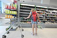 """A shopper looks at empty shelves where chilled foods would normally be stocked, inside a Waitrose supermarket in London on September 7, 2021. - Sparse shelves in some shops, empty shelves in others: the shortages affecting UK businesses are also seen in supermarkets across the country, a consequence of the pandemic and Brexit. """"We had already decided to reduce our stock because of the Covid, but now we are having trouble supplying ourselves with certain products because they are simply not available"""", laments Satyan Patel, manager of a mini-market in the center of London. (Photo by JUSTIN TALLIS / AFP) / TO GO WITH AFP STORY BY Olivier DEVOS"""