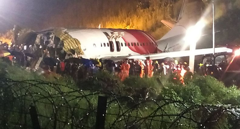 First responders gather around the wreckage of an Air India Express jet, which was carrying more than 190 passengers and crew from Dubai, after it crashed by overshooting the runway at Calicut International Airport in Karipur, Kerala, on August 7, 2020. - At least 14 people died and 15 others were critically injured when a passenger jet skidded off the runway after landing in heavy rain in India, police said on August 7. (Photo by - / AFP)