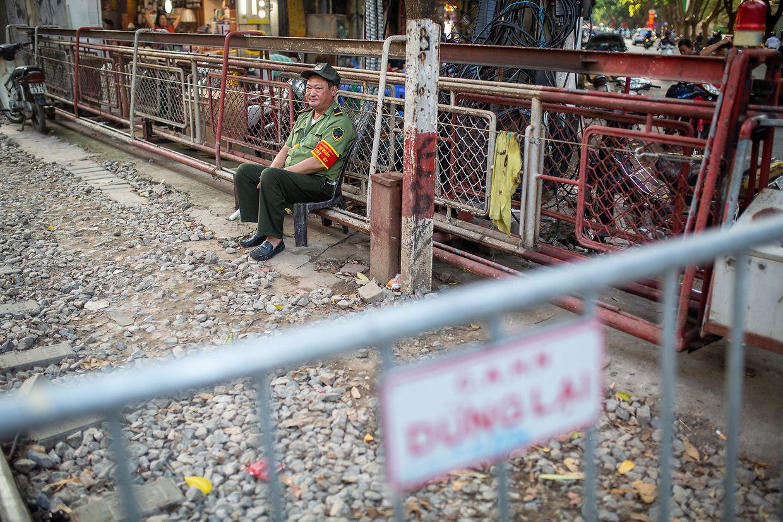 """Ein Polizist sitzt hinter der Absperrung zur """"Train Street""""."""