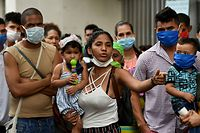 "Venezuelan migrants wait to be checked by health workers to rule out the novel coronavirus as part of their repatriation process in Cali, Colombia on April 13, 2020. - The Mayor of Cali, Jorge Ivan Ospina, announced Sunday a ""humanitarian corridor"" was started to repatriate Venezuelan migrants. (Photo by Luis ROBAYO / AFP)"